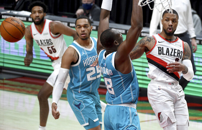 Portland Trail Blazers guard Damian Lillard, right, passes the ball over Charlotte Hornets center Bismack Biyombo, second from right, as Hornets forward P.J. Washington looks on during the second half of an NBA basketball game in Portland, Ore., Monday, March 1, 2021. (AP Photo/Steve Dykes)