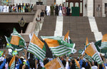 People wave Kashmiri flags as Prime Minister Imran Khan, wearing black waistcoats, attends Kashmir rally at the Prime Minister office in Pakistan, Friday, Aug. 30, 2019. Khan said he had warned the international community that India could launch an attack on Pakistani-held Kashmir in an effort to divert the attention from human rights abuses in its portion of the disputed Himalayan region. (AP Photo/B.K. Bangash)