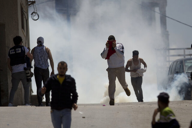 Palestinians run away from tear gas fired by Israeli soldiers during clashes after a soldier was killed when a rock thrown off a rooftop struck him in the head g during an arrest raid, in the village of Yabad near the West Bank city of Jenin, Tuesday, May. 12, 2020. Tuesday's raid was aimed at arresting four Palestinians wanted for stone-throwing at Israeli vehicles and other recent attacks. (AP Photo/Majdi Mohammed)
