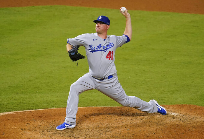 FILE - In this Aug. 15, 2020, file photo, Los Angeles Dodgers reliever Jake McGee throws during the team's baseball game against the Los Angeles Angels in Anaheim, Calif. McGee is guaranteed $5 million in his two-year contract with the San Francisco Giants and could earn $10.5 million over three seasons, including performance bonuses. (AP Photo/Marcio Jose Sanchez, File)