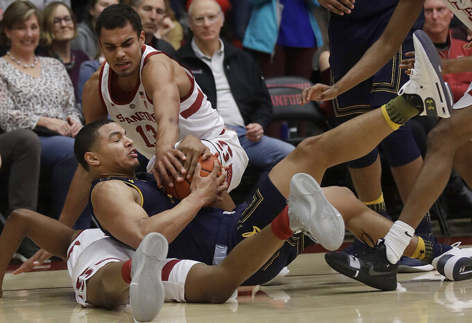 California guard Matt Bradley, center, tries to control the ball between Stanford forward Oscar Da Silva, top, and KZ Okpala during the first half of an NCAA college basketball game in Stanford, Calif., Thursday, March 7, 2019. (AP Photo/Jeff Chiu)