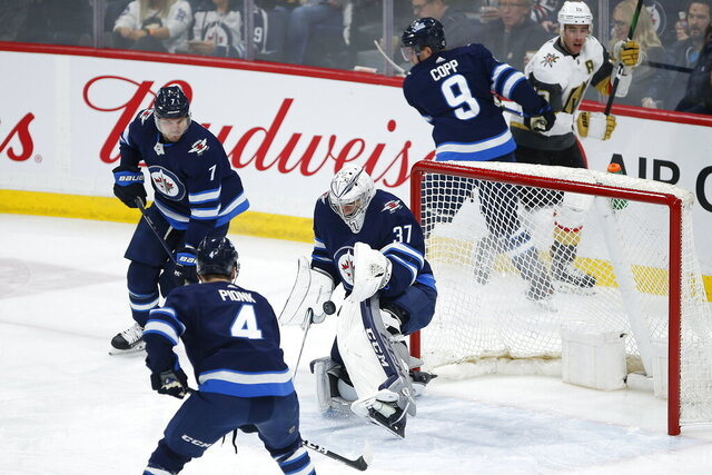Winnipeg Jets goaltender Connor Hellebuyck (37) makes a save as Dmitry Kulikov (7) and Neal Pionk (4) defend against the Vegas Golden Knights during the first period of an NHL hockey game Friday, March 6, 2020, in Winnipeg, Manitoba. (John Woods/The Canadian Press via AP)