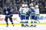 Vancouver Canucks' J.T. Miller (9) celebrates his goal with teammates Brock Boeser (6), Elias Pettersson (40) and Troy Stecher (51) during the second period of an NHL hockey game against the Winnipeg Jets, Friday, Nov. 8, 2019 in Winnipeg, Manitoba. (John Woods/Canadian Press via AP)
