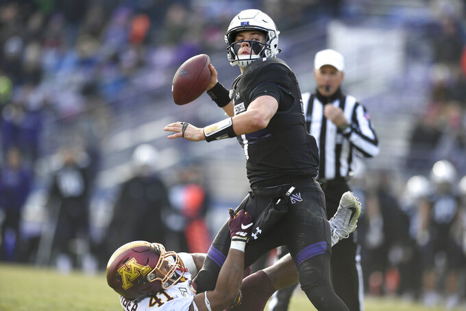 Northwestern quarterback Andrew Marty (7) throws for a 2-point conversion while in the grasps of Minnesota linebacker Thomas Barber (41) during the second half of an NCAA football game Saturday, Nov. 23, 2019, in Evanston, Ill. Minnesota won 38-22. (AP Photo/Paul Beaty)