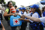 A woman with a child receives an empty container for water and water purification pills during the Red Cross' first aid shipment in Caracas, Venezuela, Tuesday, April 16, 2019. In late March, the Red Cross federation announced it would soon begin delivering assistance to an estimated 650,000 people and vowed that it would not accept interference from either side of the polarized country. (AP Photo/Ariana Cubillos)