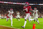 Alabama wide receiver Jerry Jeudy (4) scores on a pass reception against Arkansas during the first half of an NCAA college football game, Saturday, Oct. 26, 2019, in Tuscaloosa, Ala. Arkansas defensive back Joe Foucha (7) and Arkansas defensive back Kamren Curl (2) trail on the play. (AP Photo/Vasha Hunt)