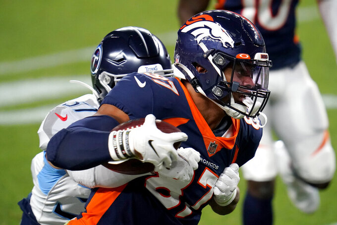 Denver Broncos tight end Noah Fant (87) is hit by Tennessee Titans safety Amani Hooker during the first half of an NFL football game, Monday, Sept. 14, 2020, in Denver. (AP Photo/David Zalubowski)