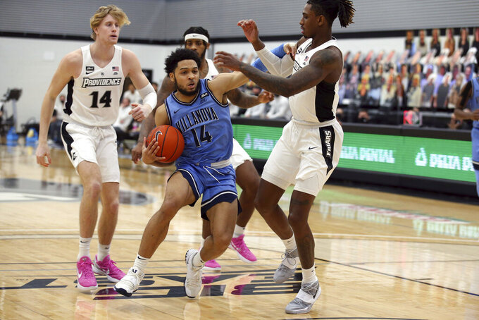 Villanova's Caleb Daniels (14) drives to the basket as Providence's Greg Gantt (1) and Noah Horchler (14) defend during an NCAA college basketball game in Providence, R.I., Saturday, March 6, 2021. (AP Photo/Stew Milne)