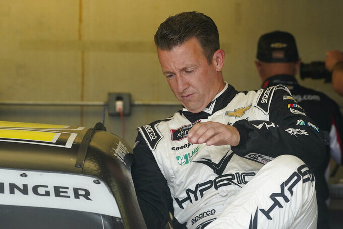 AJ Allmendinger climbs into his car before practice for the NASCAR Xfinity Series auto race at Indianapolis Motor Speedway, Friday, Aug. 13, 2021, in Indianapolis. (AP Photo/Darron Cummings)