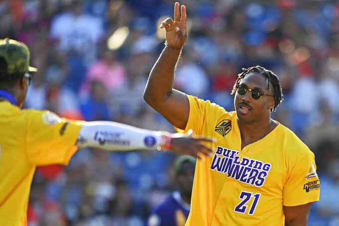 Cleveland Browns defense end Myles Garrett celebrates after hitting a home run during the Jarvis Landry Celebrity Softball game Saturday, June 12, 2021, in Eastlake, Ohio. (AP Photo/David Dermer)