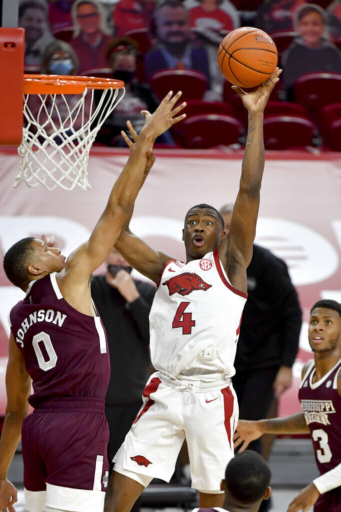 Arkansas guard Davonte Davis (4) shoots over Mississippi State defender Jalen Johnson (0) during the first half of an NCAA college basketball game Tuesday, Feb. 2, 2021, in Fayetteville, Ark. (AP Photo/Michael Woods)