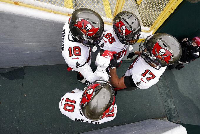 Tampa Bay Buccaneers' Justin Watson (17), Scott Miller (10), Tyler Johnson (18) and Jaydon Mickens (85) huddle before heading to the field for the NFC championship NFL football game against the Green Bay Packers in Green Bay, Wis., Sunday, Jan. 24, 2021. (AP Photo/Morry Gash)