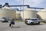 Toledo Fire and Rescue personnel on the scene where two workers died after they were trapped in a silo filled with grain, Friday, July 19, 2019 in Toledo, Ohio.  The workers became trapped Friday morning inside the silo operated by The Andersons. (Dave Zapotosky /The Blade via AP)