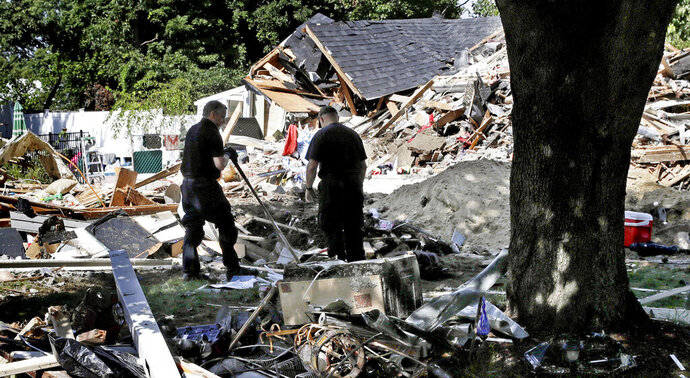 FILE - In this Sep. 21, 2018, file photo, fire investigators pause while searching the debris at a home which exploded following a gas line failure in Lawrence, Mass. Federal officials are discussing their findings from a yearlong investigation into last September's natural gas explosions and fires in Massachusetts. The National Transportation Safety Board meets in Washington, D.C., on Tuesday, Sept. 24, 2019, to discuss and vote on its final report about the Sept. 13, 2018, incident.  (AP Photo/Charles Krupa, File)