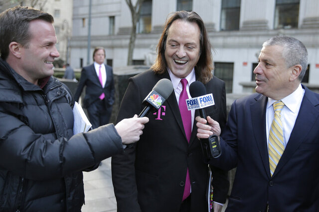 FILE - In this Jan. 15, 2020, file photo T-Mobile chief executive John Legere speaks to reporters as he leaves the courthouse in New York. A federal judge has removed a major obstacle to T-Mobile's $26.5 billion takeover of Sprint, as he rejected claims by a group of states that the deal would mean less competition and higher phone bills. (AP Photo/Seth Wenig, File)
