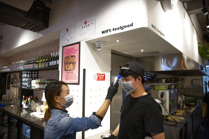 Manager Chen Tiantian measures an employee's temperature at a Moka Bros cafe in Beijing, Friday, Feb. 14, 2020. For Valentine's Day Moka Bros, a health food eatery in Beijing, offered a special that included both a rose and a note logging the temperature of the chef that made the meal. Like many businesses in China, the restaurant has struggled to cope with the impact of a virus that has infected tens of thousands of people worldwide and sent several cities into lockdown. (AP Photo/Mark Schiefelbein)