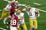 Alabama linebacker Christopher Allen (4) grabs the face mask of Notre Dame wide receiver Ben Skowronek (11) in the second half of the Rose Bowl NCAA college football game in Arlington, Texas, Friday, Jan. 1, 2021. (AP Photo/Roger Steinman)
