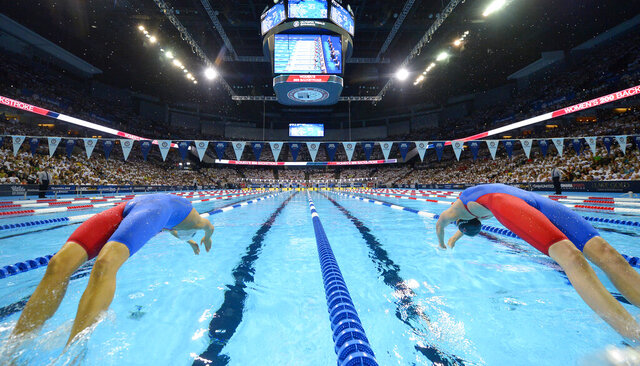 FILE - In this July 1, 2016, file photo, Elizabeth Beisel, left, and Missy Franklin start the women's 200-meter backstroke semifinal at the U.S. Olympic swimming trials in Omaha, Neb. The U.S. Olympic swimming trials will be split into two meets, a radical change that is designed to provide safer conditions in the midst of the coronavirus pandemic. USA Swimming announced Tuesday, Jan. 26, 2021, that a Wave I meet, comprised of lower-ranked swimmers qualifying for the trials, will be held on June 4-7. The top finishers will advance to the main Wave II meet on June 13-20 to determine who represents the U.S at the Tokyo Games. (AP Photo/Mark J. Terrill, File)