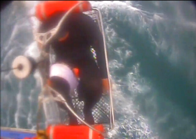 In this Saturday, Dec. 21, 2019, image taken from video released by the U.S. Coast Guard, a man, wearing a full-body wetsuit, is hoisted up from a boat into a helicopter near Santa Rosa Island, one of the Channel Islands in Southern California. A shark reportedly bit the surfer Saturday afternoon in a