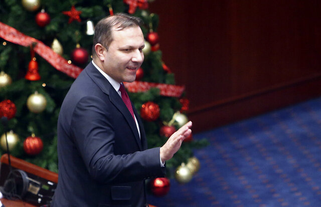 Oliver Spasovski, the new prime minister of the caretaker government, greets the lawmakers after the parliament voted in favor on a session in Skopje, North Macedonia, Friday, Jan. 3, 2020. The prime minister of North Macedonia Zoran Zaev submitted his resignation Friday, paving the way for a new caretaker Cabinet to be named in order to organize a snap election. (AP Photo/Boris Grdanoski)