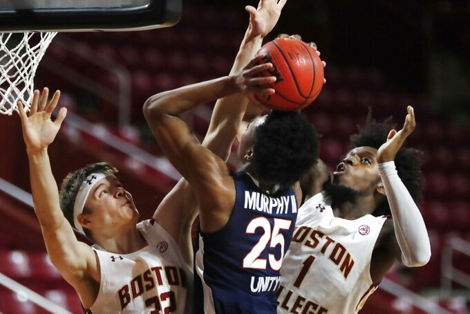 Boston College's Justin Vander Baan, left,  and CJ Felder, right, block a shot by Virginia's Trey Murphy III, center, during the first half of an NCAA college basketball game, Saturday, Jan. 9, 2021, in Boston. (AP Photo/Michael Dwyer)