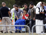 Zaed Mustafa, in wheelchair, brother of Hamza and son of Khalid Mustafa killed in the Friday March 15 mosque shootings reacts during the burial at the Memorial Park Cemetery in Christchurch, New Zealand, Wednesday, March 20, 2019. (AP Photo/Mark Baker)