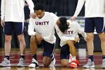Virginia players kneel during the national anthem before an NCAA college basketball game against Boston College, Saturday, Jan. 9, 2021, in Boston. (AP Photo/Michael Dwyer)