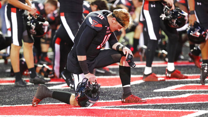 Texas Tech quarterback Alan Bowman says a prayer before the team's NCAA college football game against Oklahoma, Saturday, Oct. 31, 2020, in Lubbock, Texas. (AP Photo/Mark Rogers)