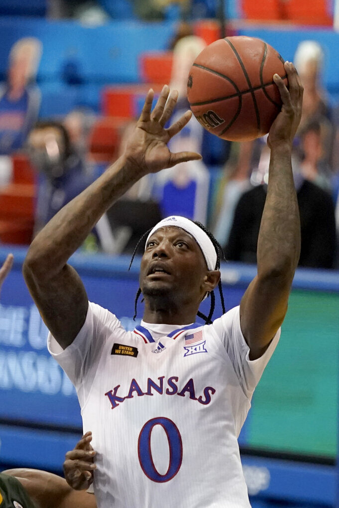 Kansas' Marcus Garrett (0) gets past North Dakota State's Tyree Eady to shoot during the first half of an NCAA college basketball game Saturday, Dec. 5, 2020, in Lawrence, Kan. (AP Photo/Charlie Riedel)