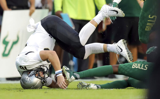UCF's quarterback McKenzie Milton goes down with an apparent knee injury after being tackled during the first half of an NCAA college football game against South Florida, Friday, Nov. 23, 2018, in Tampa, Fla. (AP Photo/Mike Carlson)