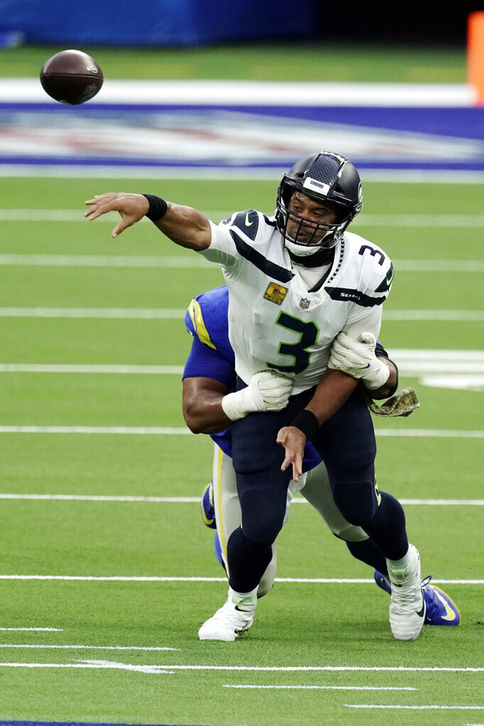 Seattle Seahawks quarterback Russell Wilson (3) throws as he is tackled by Los Angeles Rams defensive end Aaron Donald during the second half of an NFL football game Sunday, Nov. 15, 2020, in Inglewood, Calif. (AP Photo/Jae C. Hong)