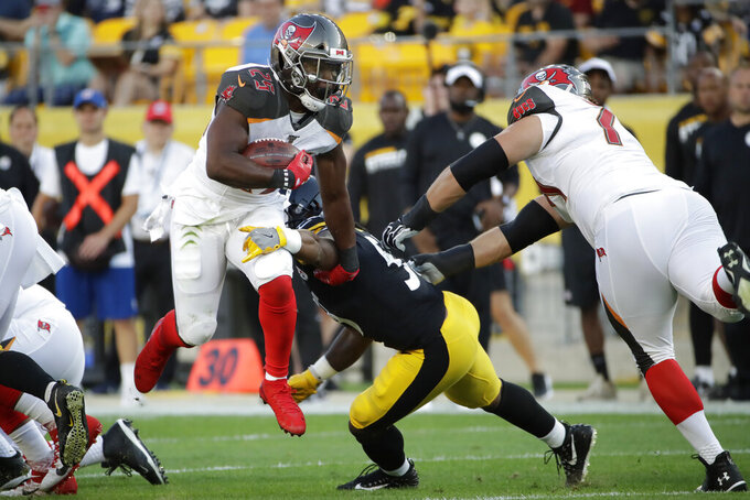 Tampa Bay Buccaneers running back Peyton Barber (25) is tackled by Pittsburgh Steelers linebacker Ulysees Gilbert (54) during the first half of an NFL preseason football game in Pittsburgh, Friday, Aug. 9, 2019. (AP Photo/Don Wright)