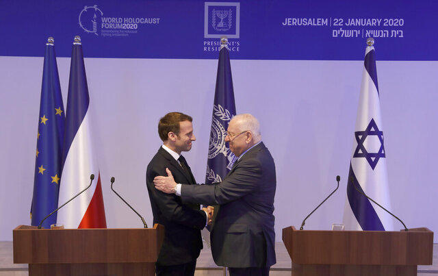 French President Emmanuel Macron, left, and Israeli President Reuven Rivlin, greet each other ahead of the World Holocaust Forum in Jerusalem, Israel on Wednesday, Jan. 23, 2020. Dozens of world leaders have descended upon Jerusalem for the largest-ever gathering focused on commemorating the Holocaust and combating modern-day anti-Semitism.  (Atef Safadi/Pool Photo via AP)
