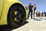 Driver Tommy Milner, right foreground, talks with General Motors personnel following a news conference at Raceway at Belle Isle in Detroit, Wednesday, June 9, 2021. In the foreground is a 2022 Corvette Stingray IMSA GTLM Championship Edition road car. (AP Photo/Jose Juarez)
