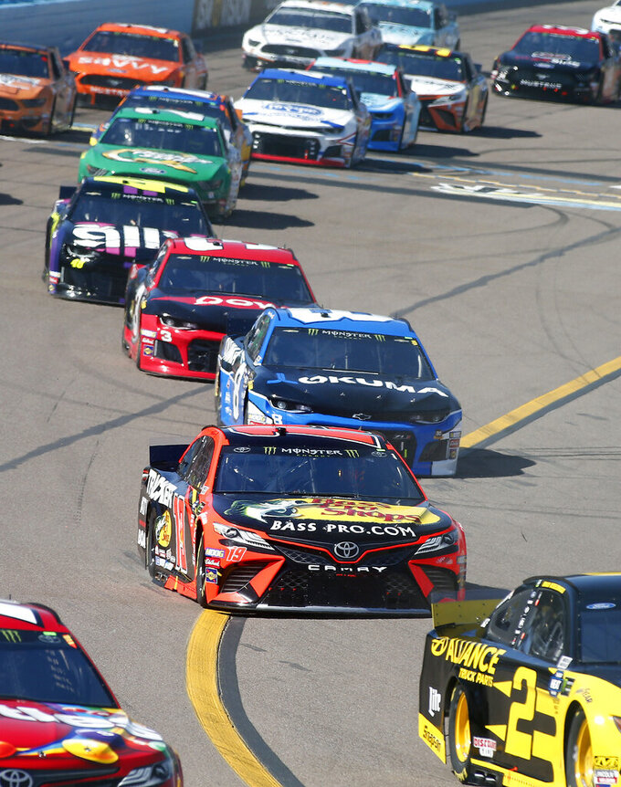 Martin Truex Jr. (19) drives to the inside of the track in a pack of cars during the NASCAR Cup Series auto race at ISM Raceway, Sunday, March 10, 2019, in Avondale, Ariz. (AP Photo/Ralph Freso)