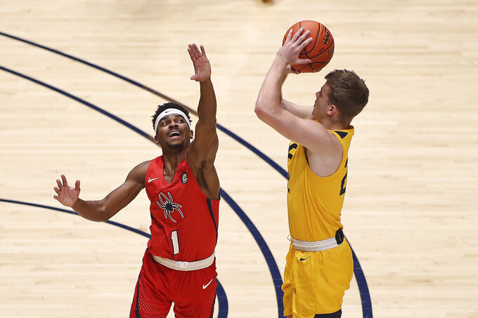 West Virginia guard Sean McNeil (22) shoots while defended by Richmond guard Blake Francis (1) during the first half of an NCAA college basketball game Sunday, Dec. 13, 2020, in Morgantown, W.Va. (AP Photo/Kathleen Batten)