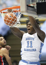 North Carolina's Day'Ron Sharpe (11) dunks next to Northeastern's Jason Strong (00) during the first half of an NCAA college basketball game Wednesday, Feb. 17, 2021, in Chapel Hill, N.C. (Robert Willett/The News & Observer via AP)