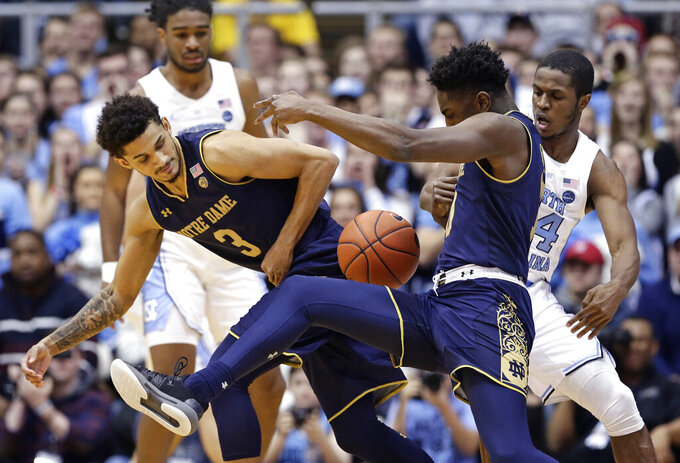 North Carolina's Kenny Williams, right, reaches in on Notre Dame's TJ Gibbs as Prentiss Hubb (3) looks for the ball during the first half of an NCAA college basketball game in Chapel Hill, N.C., Tuesday, Jan. 15, 2019. (AP Photo/Gerry Broome)