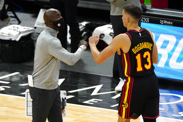 Atlanta Hawks coach Lloyd Pierce, left, celebrates with guard Bogdan Bogdanovic during the first half of the team's NBA basketball game against the Chicago Bulls in Chicago, Wednesday, Dec. 23, 2020. (AP Photo/Nam Y. Huh)