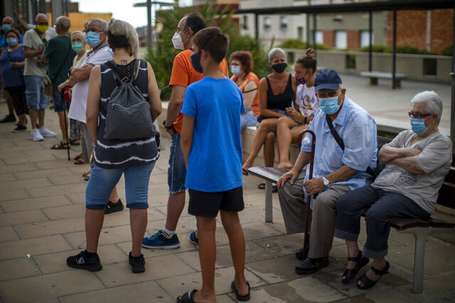 People wearing face masks wait their turn to be called for a PCR test for the COVID-19 outside a local clinic in Santa Coloma de Gramanet in Barcelona, Spain, Tuesday, Aug. 11, 2020. (AP Photo/Emilio Morenatti)