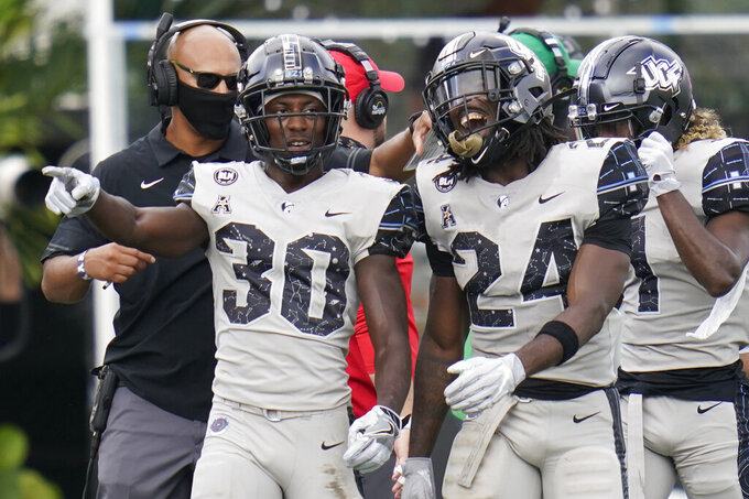 Central Florida running back Greg McCrae (30) celebrates his 3-yard touchdown run against Tulane with teammate running back Bentavious Thompson (24) during the first half of an NCAA college football game, Saturday, Oct. 24, 2020, in Orlando, Fla. (AP Photo/John Raoux)