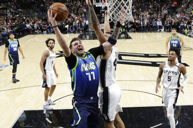 Dallas Mavericks guard Luka Doncic (77) drives to the basket against San Antonio Spurs center Trey Lyles (41) during the second half of an NBA basketball game in San Antonio, Wednesday, Feb. 26, 2020. (AP Photo/Eric Gay)