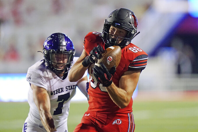 Utah tight end Dalton Kincaid (86) catches a pass as Weber State safety Preston Smith (7) defends during the second half of an NCAA college football game Thursday, Sept. 2, 2021, in Salt Lake City. (AP Photo/Rick Bowmer)