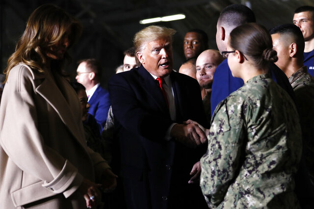President Donald Trump greets people after signing the National Defense Authorization Act for Fiscal Year 2020 at Andrews Air Force Base, Md., Friday, Dec. 20, 2019, before traveling to Mar-a-lago in Palm Beach, Fla. At left is first lady Melania Trump. (AP Photo/Andrew Harnik)