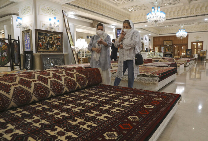 Customers look at rugs at a hand crafts store at Iran Mall shopping center in Tehran, Iran, Wednesday, June 9, 2021. The West considers Iran's nuclear program and Mideast tensions as the most important issues facing Tehran, but those living in the Islamic Republic repeatedly point to the economy as the major issue facing it ahead of its June 18 presidential election.  (AP Photo/Vahid Salemi)