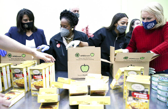Texas congresswoman Penny Morales Shaw, from left, joins U.S. Representatives Sheila Jackson Lee, Alexandria Ocasio-Cortez and Sylvia Garcia,  as they fill boxes at the Houston Food Bank on Saturday, Feb. 20, 2021.   President Joe Biden declared a major disaster in Texas on Friday, directing federal agencies to help in the recovery.  (Elizabeth Conley/Houston Chronicle via AP)