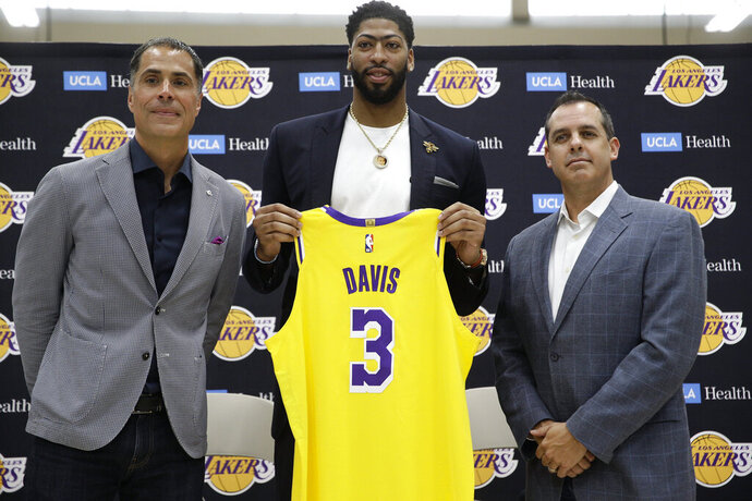 Los Angeles Lakers NBA basketball team general manager Rob Pelinka, left, and Head Coach Frank Vogel, right, introduce Anthony Davis at a news conference at the UCLA Health Training Center in El Segundo, Calif., Saturday, July 13, 2019 (AP Photo/Damian Dovarganes)