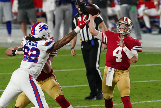 San Francisco 49ers quarterback Nick Mullens (4) throws as Buffalo Bills defensive end Darryl Johnson (92) defends during the second half of an NFL football game, Monday, Dec. 7, 2020, in Glendale, Ariz. (AP Photo/Ross D. Franklin)