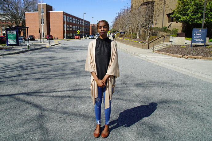 "Sophomore political-science major Kylah Guion stands in the middle of Laurel Street in Greensboro, N.C., on Tuesday, March 19, 2019. Gerrymandering has cut the campus of North Carolina A&T University in half, with this street as the dividing line between the 6th Congressional District on her left and the 13th District on her right, both represented by Republicans. ""It's hard to explain to students who are already skeptical about the voting process ... that the state intentionally diluted their power in voting by putting this line back here in between our campus,"" she says. (AP Photo/Allen G. Breed)"