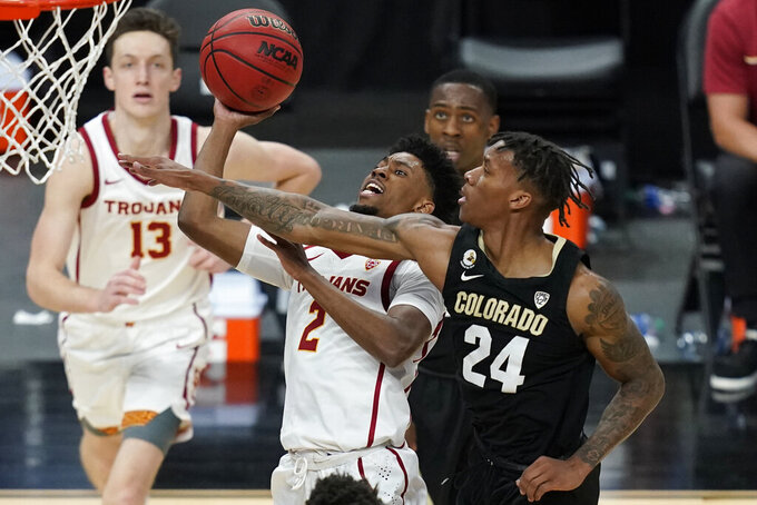 Colorado's Eli Parquet (24) guards Southern California's Tahj Eaddy (2) during the second half of an NCAA college basketball game in the semifinal round of the Pac-12 men's tournament Friday, March 12, 2021, in Las Vegas. (AP Photo/John Locher)